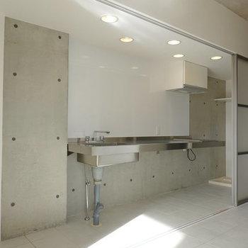 コンクリ壁にステンレスキッチン。冷蔵庫は左手に置けます。(※写真は10階の反転間取り別部屋のものです)