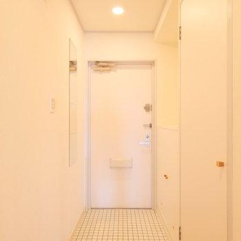 玄関も白い磁器タイルでスッキリとした佇まい。身だしなみがチェックできる姿見が嬉しい!