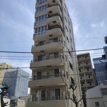 通り沿いに建つ、背の高いマンション。