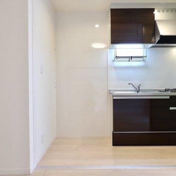 反対側を向くと、少し奥まった位置に濃いブラウンのキッチンが!左手は家電用のスペース。