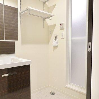 その横にはパン無しタイプの洗濯機置き場。上にはバー付きの便利な棚も付いています。