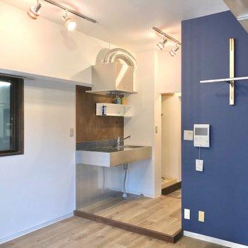 廊下部分は一段上がったところに。ステンレスのキッチンがおしゃれです。