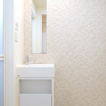 タイルの壁のホテルライクな脱衣所には、バーチカルミラーのコンパクトな洗面台が……!
