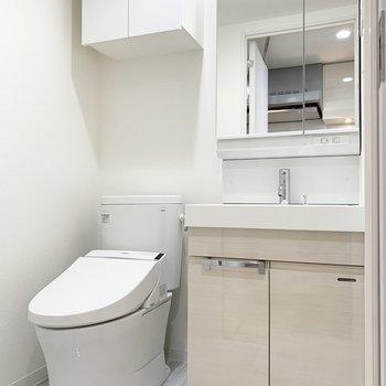 温水洗浄便座付きのトイレと鏡の大きい独立洗面台。