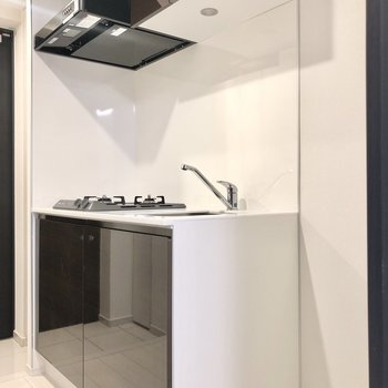 キッチンはダークブラウン。横に冷蔵庫が置けます。※写真は4階の反転間取り別部屋のものです