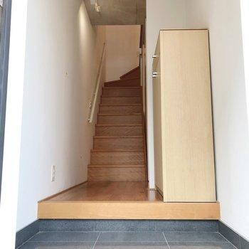 玄関を入ると階段がお出迎え。右側には水回り。(※写真は1階の同間取り別部屋のものです)