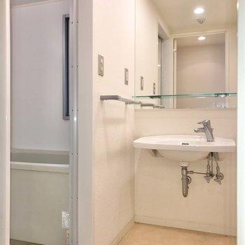 手前は脱衣所。洗面台もミニマムデザインで素敵。(※写真は清掃前のものです)