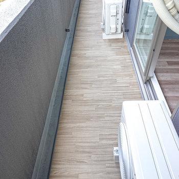 集成材のような模様が清潔な雰囲気のあるベランダ。物干し竿もついています。(※写真は2階の同間取り別部屋のものです)