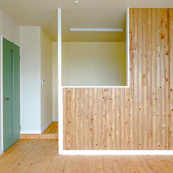 窓側から。対面式キッチンの壁にも杉材が。モスグリーンのドアも素敵。(※写真は2階の同間取り別部屋のものです)