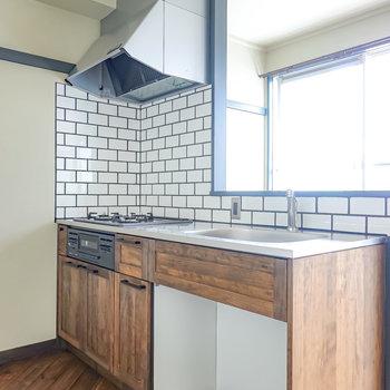 壁の向こうには深い色合いの無垢材を使ったキッチン。木目の表情が美しい。