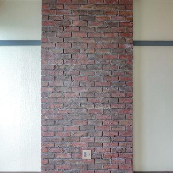 本物のレンガが積まれた壁。テレビ線があるので、テレビとソファでホームシアターに。