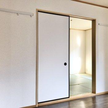 【洋室】引き戸の両側にはピクチャーレール。時計やドライフラワーなどを掛けても良さそう。