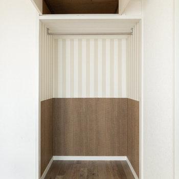 オープンクローゼット。上部には収納棚もあります。ストライプの壁紙がキュートですね。