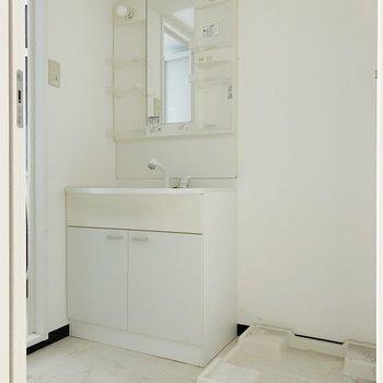 脱衣スペースには洗面台と洗濯機置き。(※写真は清掃前のものです)