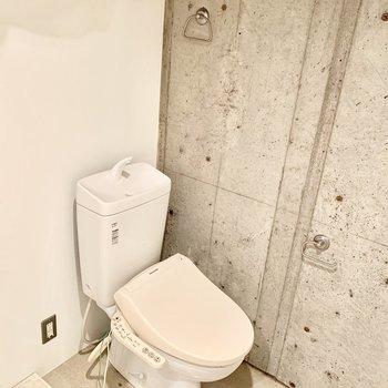 洗濯機とトイレが並びます。※クリーニング前の写真です