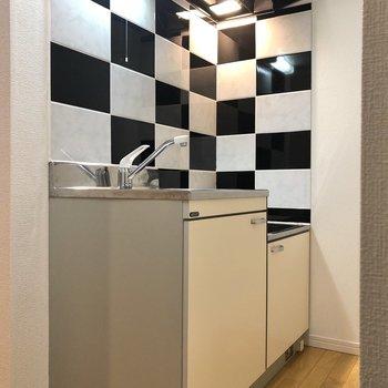 黒と白のタイルが印象的なキッチンへ。