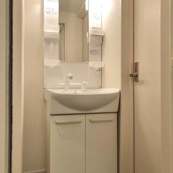 白で統一された洗面台。歯ブラシなどの小物が置ける棚もあります。
