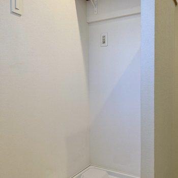 洗濯機置き場は玄関のとなりに。棚付きなので洗濯洗剤等も並べられますね。