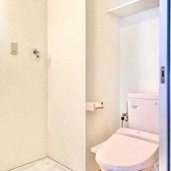 隣は室内洗濯機置き場と、あ、こちらにもピンクのトイレが。 温水洗浄便座になっていますよ。