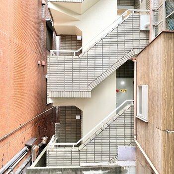 窓からは周辺のマンションが。階段にいる人と目があってしまうかも。