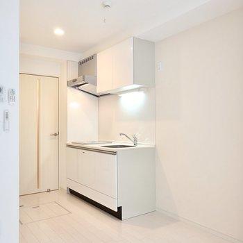 キッチンは玄関側に。白いパネルが美しい。右手のスペースにキッチン家電がたっぷり置けます。
