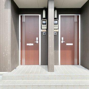 玄関ドアはブラウンでナチュラルな印象。