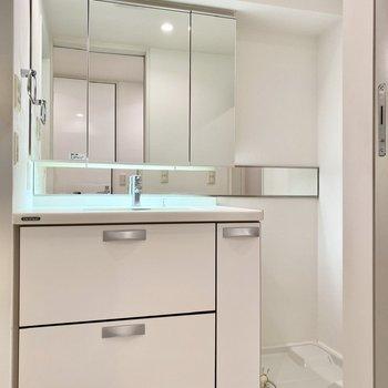ワイドな印象の洗面台。鏡が洗濯機置き場の方まで伸びているのが特徴的です。