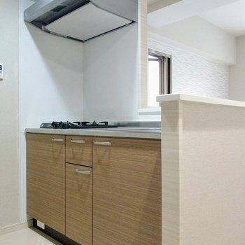 木目調のカウンターキッチン。コンロは2口あります。(※写真は2階の同間取り別部屋のものです)