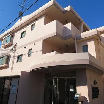 低層のマンションです。ほのかにピンク