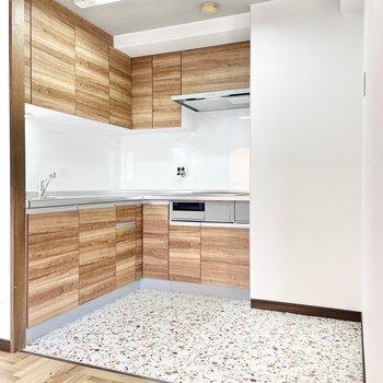 L字型キッチンは木目調がアクセントに。