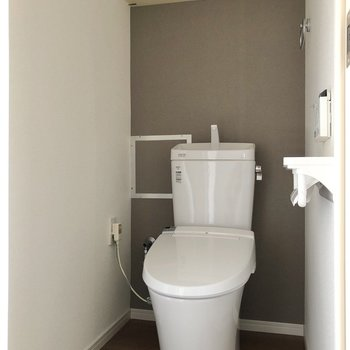 グレーがアクセントのトイレには上部収納付き。