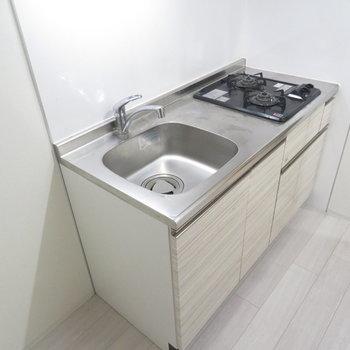 2口コンロのシステムキッチン。隣には冷蔵庫スペースが(※写真は3階の同間取り別部屋のものです)