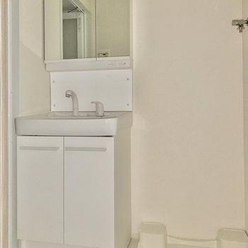 サニタリールームには洗面台と洗濯機置場がぴったりと納まっています。※写真は通電前のため、フラッシュ撮影をしています