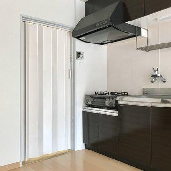 脱衣所へはキッチン横のアコーディオンカーテンを開けて(※写真は清掃前のものです)