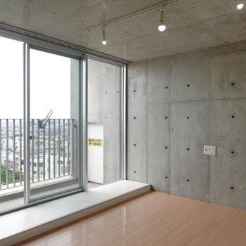 壁も天井もコンクリ打ちっ放し。テレビは壁掛けでスタイリッシュに。(※写真は10階の同間取り別部屋のものです)