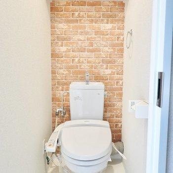 レンガ調クロスのあるウォシュレット付きトイレ。遊び心が凄い。(※写真は10階の同間取り別部屋のものです)