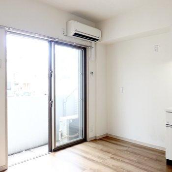 中は白い空間に飴色のフローリングが映えるシンプルなお部屋。