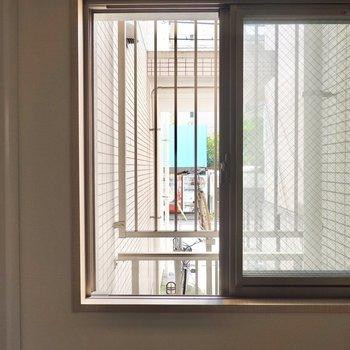 洋室の窓の外は共用部の駐輪場。