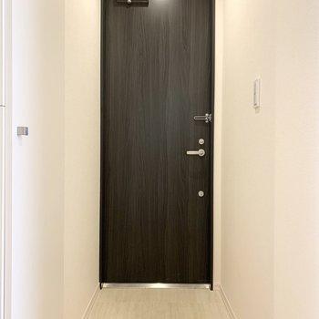 ダークトーンな木調のドアが素敵な玄関。(※写真は3階の同間取り別部屋のものです)