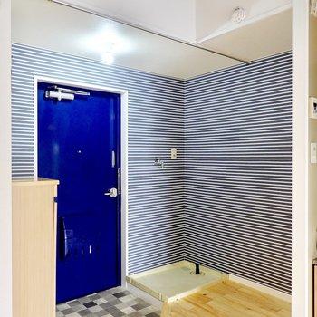 玄関周りは青いドアとボーダー柄のクロス、白色光のライトで清涼感のある雰囲気に。洗濯機置場もこちらにあります。