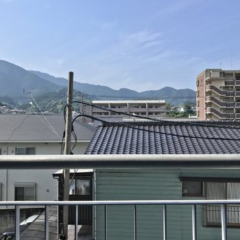 住宅街の先に、山と広い空が見える素敵な景色。
