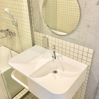 真っ白な洗面台にはまーるいミラー。(※写真は2階の同間取り別部屋のものです)