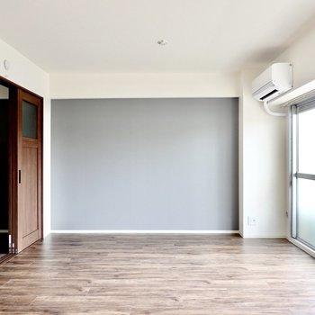 グレーの壁にはテレビとホームシアターシステムを設置して映画の世界を楽しもう。