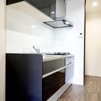 床の色に合わせた真っ黒なシステムキッチン。