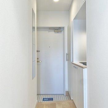 玄関は白タイル。鏡があるので身だしなみチェックもできちゃいます◎