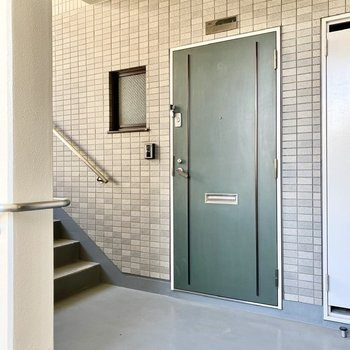 玄関前共用部。モスグリーンのドアが渋いですねえ。