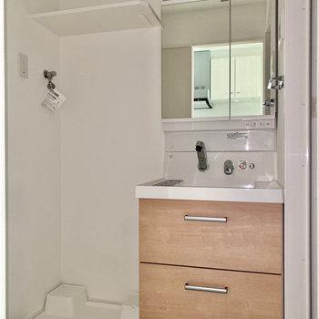 独立洗面台と室内洗濯機置き場は隣同士。※写真は通電前のもの・フラッシュを使用しています