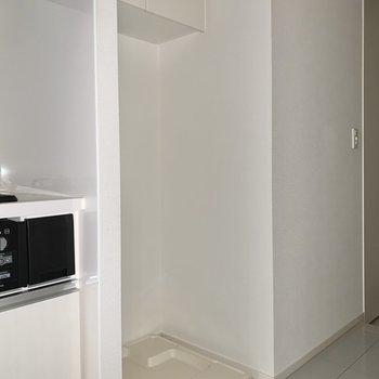 お隣に洗濯機置き場。上部棚には洗剤を。※写真はフラッシュを使用しています