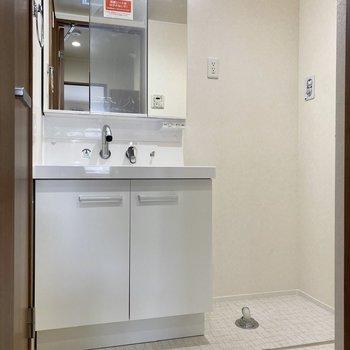 ゆったりとした脱衣所には、鏡の大きな洗面台と洗濯機置き場が。