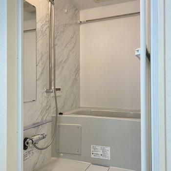 乾燥機付きの浴室。大理石調の壁材がエレガントです。